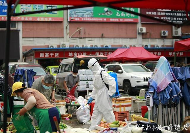 武汉太平洋农贸市场内,消防员对室外蔬菜摊位进行消杀