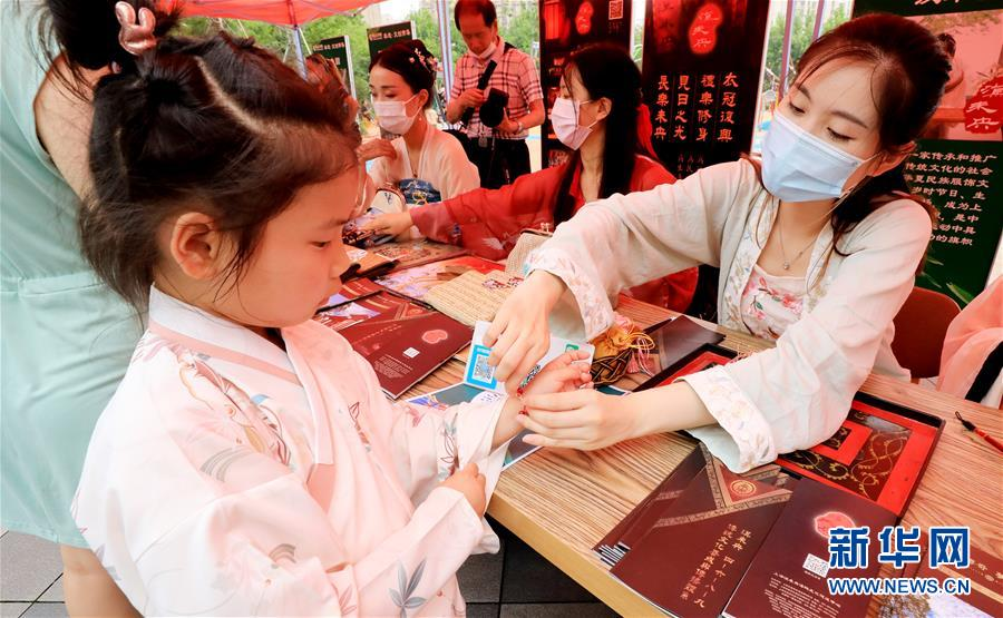 主持人(中)与工作人员(左)一起在店内通过网络直播销售粽子和糕团等食品