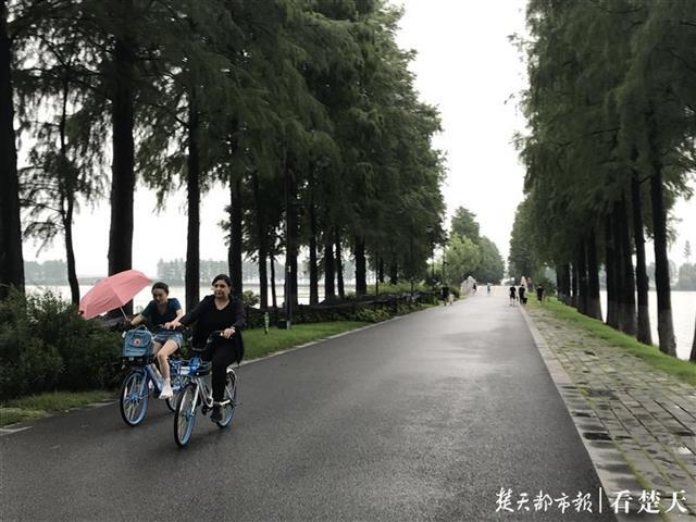 强降雨挡不住户外运动的脚步!乌云压顶,大伙儿撑伞穿雨衣骑行东湖绿道