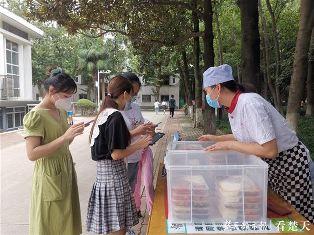 学生在食堂前排队取餐