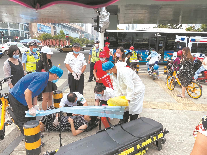 两女子骑车相撞倒在马路中 志愿者跪地托住伤者头部等救护