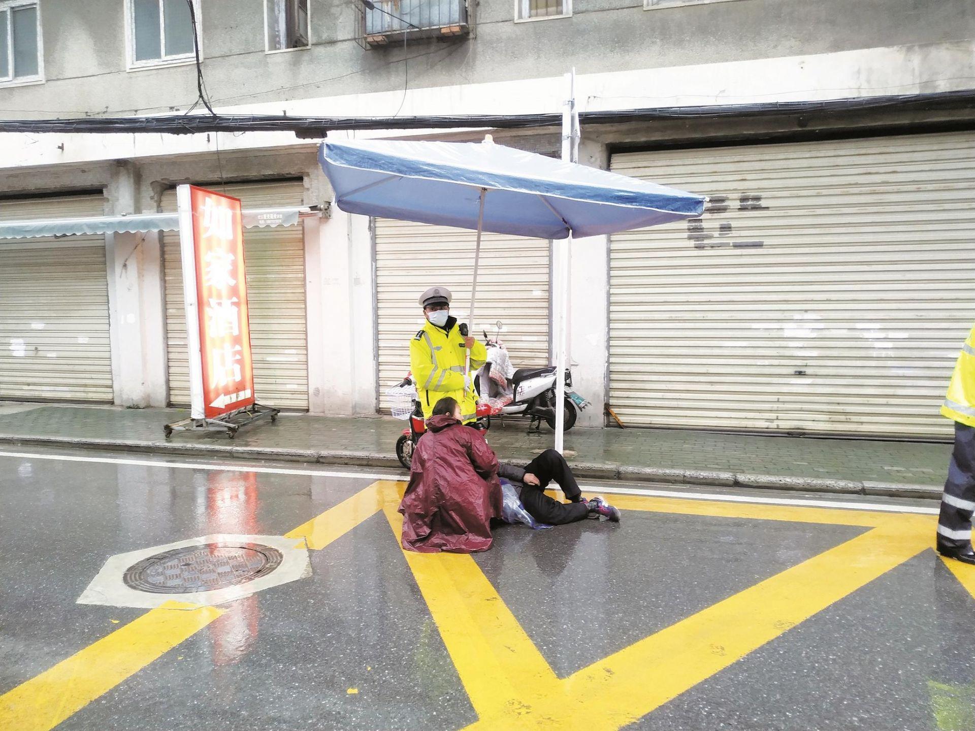 交警腰顶大伞为受伤老人遮挡寒
